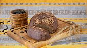 Fresh Whole-grain Bread With Seeds Cut On A Wooden Board, A Knife, Mortar With Sunflower Seeds And R poster