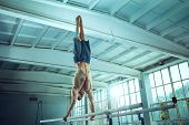 The Sportsman Performing Difficult Gymnastic Exercise At Gym. The Sport, Exercise, Gymnast, Health,  poster