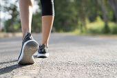 Runner Feet Running On Road Closeup On Shoe. Woman Fitness Sunrise Jog Workout Welness Concept. Youn poster