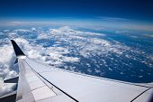 High altitude. Sky, clouds and atmosphere seen from an airplane. Ocean, white clouds, airplane wing  poster