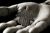 closeup of an old hamsa amulet, also known of the hand of fatima or the hand of mary, on the palm of poster
