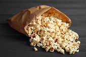 Paper Bag With Tasty Popcorn On Wooden Background poster