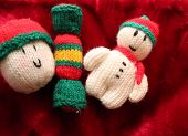stock photo of bobble head  - Three knitted christmas decorations on red background - JPG