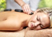 beauty, wellness and relaxation concept - close up of beautiful young woman having hot stone massage poster