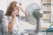 Woman suffers from heat while working in the office and tries to cool off by the fan poster