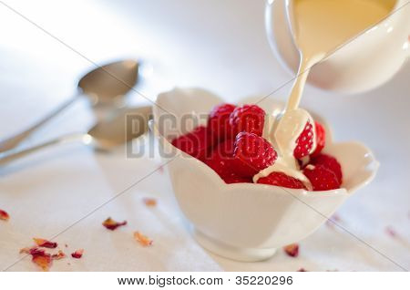 Cream Pouring From A Jug Over Fresh Rasberries