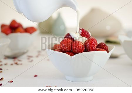 Cream Pouring From A Jug Over Fresh Strawberries