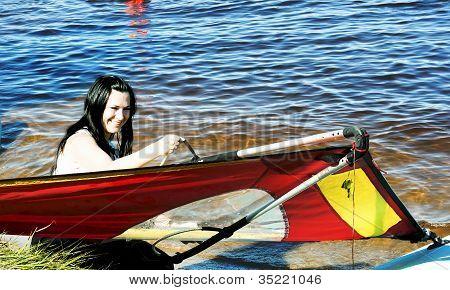 Smiling cute girl raises a sail