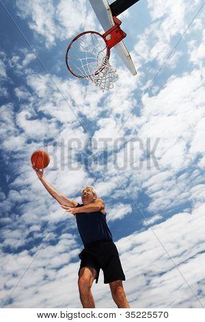 Happy active senior man playing basketball