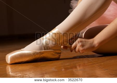 Ballerina Adjusting En Pointe Ballet Shoes (Slippers)