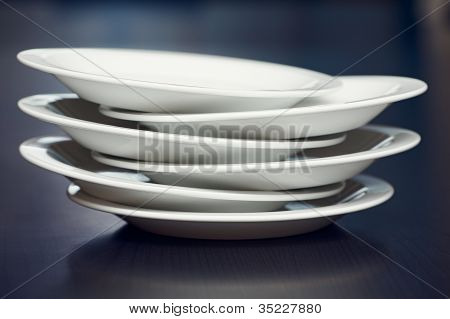 A Stack Of White Plates On A Table