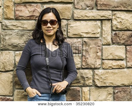 Asian Women Holding Camera Against Stone Wall