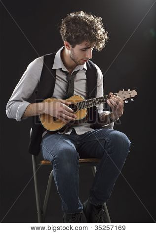 Young Man Sitting And Playing A Ukelele