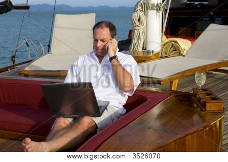 Man On Yacht With Phone And Laptop