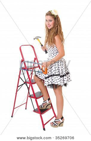 Pretty Pin Up Woman On A Ladder With A Hammer And Saw