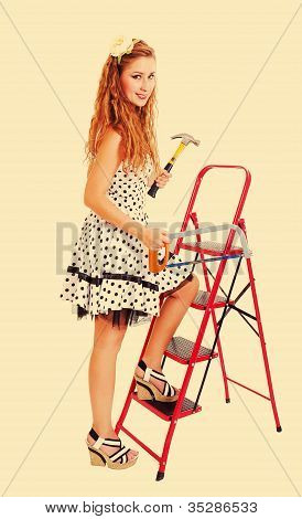 Pretty Pin Up Woman On A Ladder With A Hammer And Saw, Toned In Retro Style