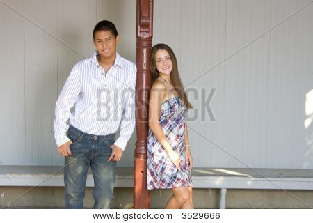 Teenage Couple Both Leaning On Red Pole