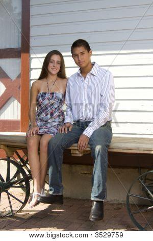 Teenage Couple Sitting Together On Wagon