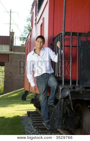 Young Man Standing On Steps Of Caboose
