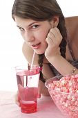 picture of halter-top  - Teenaage girl in halter top with long brown braids sips drink through a straw and looks up - JPG