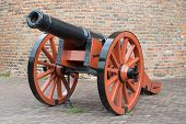 picture of artillery  - Old medieval artillery canon before a brick wall - JPG