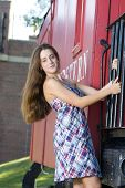 stock photo of caboose  - Attractive teenage girl in a dress standing on the steps of a red caboose - JPG