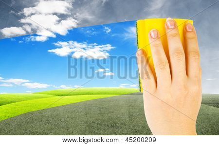 Woman hand cleaning the window with background with field. Concept of changing of mood
