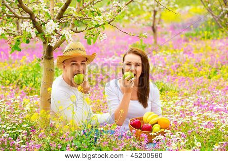 Young beautiful couple having picnic outdoors in summer time, biting fresh green apple, relaxation outdoors, love concept