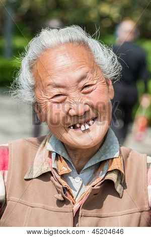 SHANGHAI, CHINA - APR 7, 2013: old chinese woman friendly toothless toothy smiling outddors portrait  at the city of Shanghai in China on april 7th, 2013