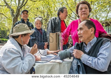 SHANGHAI, CHINA - APR 7, 2013: chinese doctor ausculting people  in fuxing park at the city of Shanghai in China on april 7th, 2013