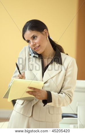 Businesswoman talking on phone and writing on legal pad