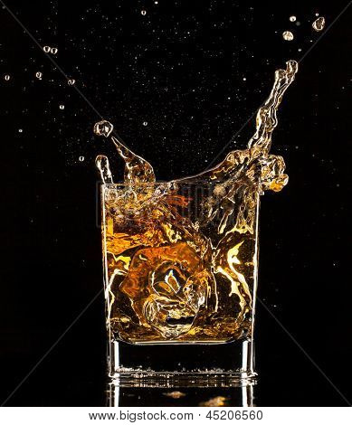 Isolated shot of whiskey splashing out of glass on black background
