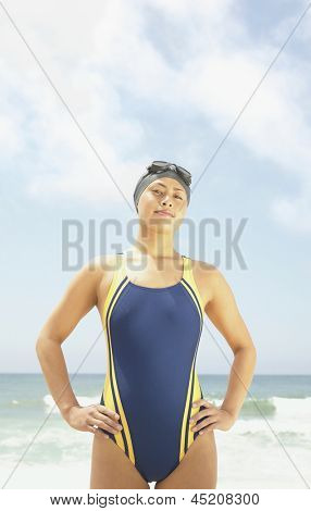 Portrait of woman in one-piece swimsuit standing at beach