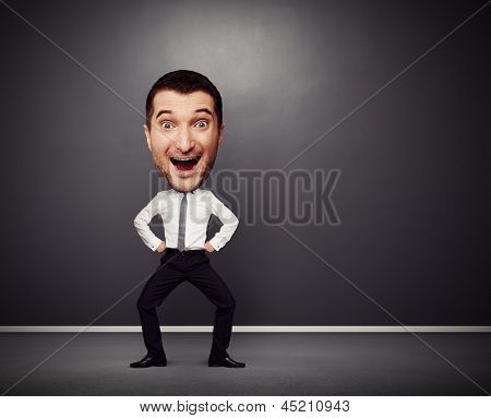 full-length funny picture of dancing businessman with big head over dark background