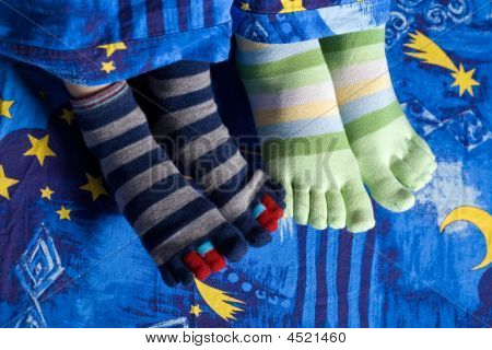 Two Pairs Of Feet In Socks
