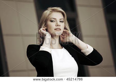 Young business woman against office windows