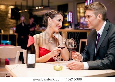 happy affectionate couple clinking glasses at restaurant toasting and looking at each other