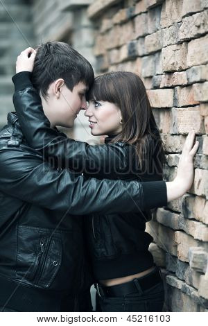 Happy young couple in love against a brick wall