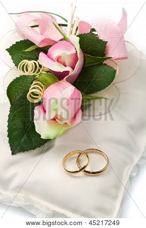 Gold Wedding Rings On White Pillow With Rose