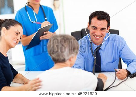 medical doctor checking senior patient's blood pressure