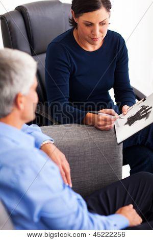 Senior hombre haciendo test de Rorschach inkblot con su terapeuta en la oficina