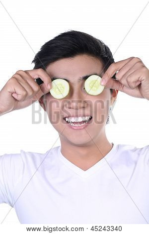 Asian young man with cucumber slices on eyes