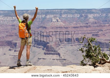 Grand Canyon hiking woman hiker happy and cheerful with arms raised up outstretched in joy. Winner and success concept with excited elated female hiker outdoors in Grand Canyon, Arizona, USA.
