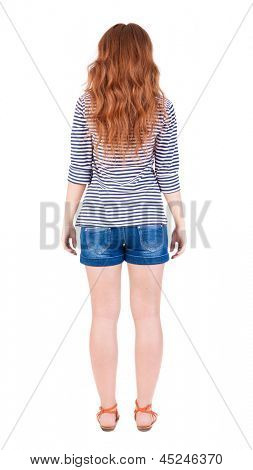 back view standing young beautiful redhead woman. girl  watching.Rear view people collection.  backside view person. Isolated over white background. red-haired teenager in striped t-shirt and sandals