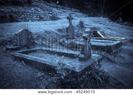 Spooky Halloween graveyard in fog in moonlight