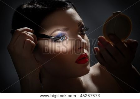 Sexy brunette in front of mirror putting mascara makeup in darkness