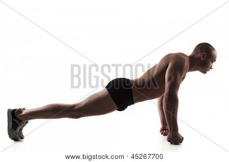 Silhouette of young man performing push-ups exercise on fists, on white background