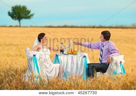 Bride and groom next to wedding table on the wheat field