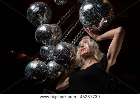 Close-up face of young blonde woman disco mirror ball in hands