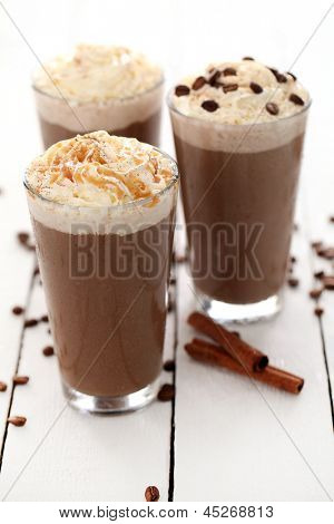 Ice coffee with whipped cream and coffee beans on a white table
